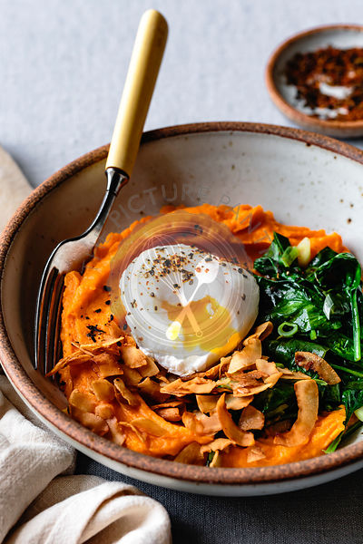 Sweet potato breakfast bowl with spinach, coconut bacon and poached egg.