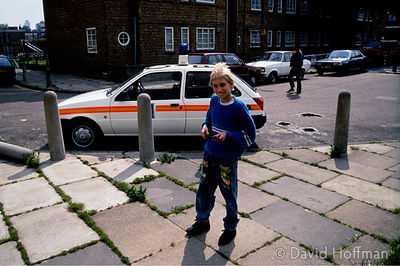 Boy playing with toy gun on the dilapidated Clapton Park Estate during school time.