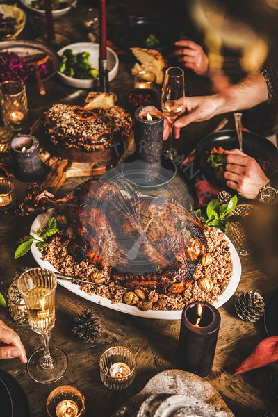 Friends celebrating Christmas over festive table with whole roasted Turkey