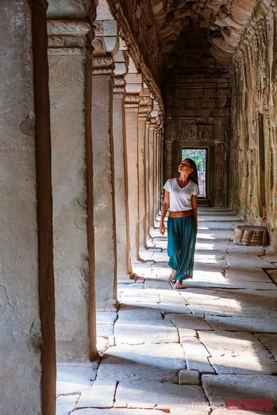 Woman walking in a corridor inside a temple, Angkor