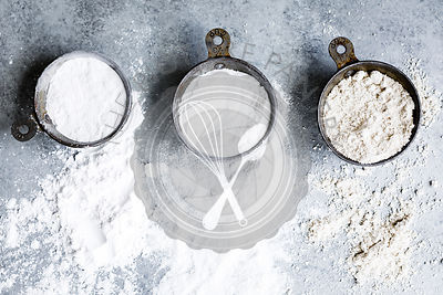 Three types of flour in measuring cups on a gray background