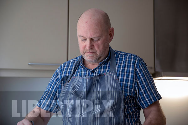 MATURE GAY MAN COOKING IN A DOMESTIC KITCHEN.