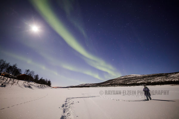 Person photographing the Aurora under the full moon on the frozen Teno River in Utsjoki in Lapland, Finland