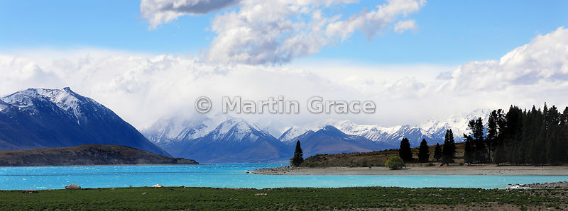 Looking North over impossibly-aquamarine glacial meltwaters of Lake Tekapo to a backdrop of Southern Alps, Canterbury, South ...
