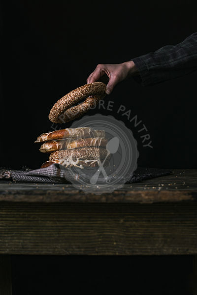 A Hand Taking a Bagel on a Black Background