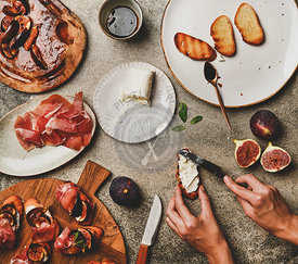 Crostini with prosciutto, figs and female hands spreading goat cheese