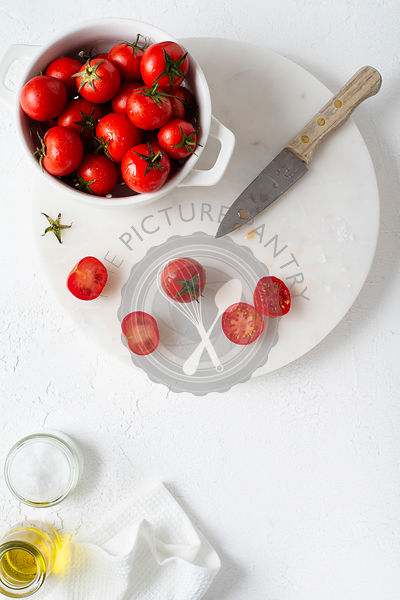 Freshly washed cherry tomatoes in a white colander, prepared for slicing. Olive oil and salt on the side. Overhead view.