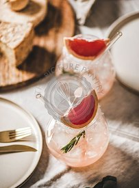 Grapefruit margaritas in glass, cheese, cutlery and dinnerware on table