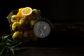 Home grown lemons in a square wire basket, on a rustic wooden background. Lemon leaves are in the foreground.