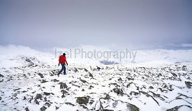 A hiker walking over the summit of High Raise towards Rampsgill Head near Hartsop in the Lake District.