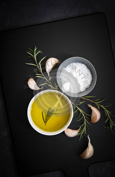 Olive oil, salt flakes, garlic cloves and rosemary.
