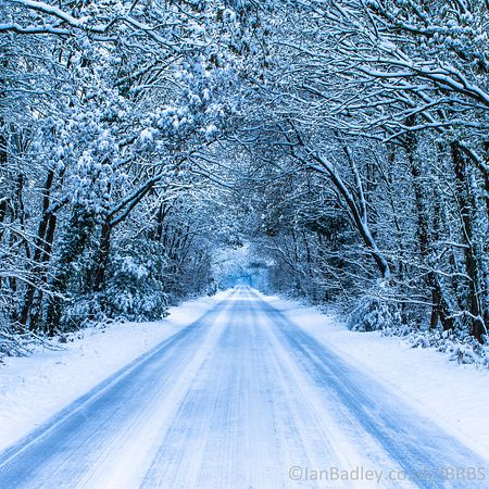 Snow covered long road