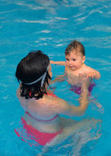 Woman and baby girl swimming together