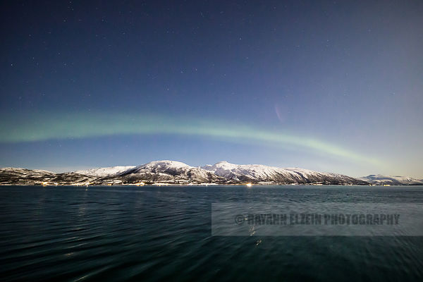 The Northern Lights (Aurora Borealis) above the mountains near Tromso, Northern Norway