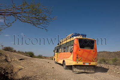 Rear view of bus traveling on dirt road, Tanzania, Africa