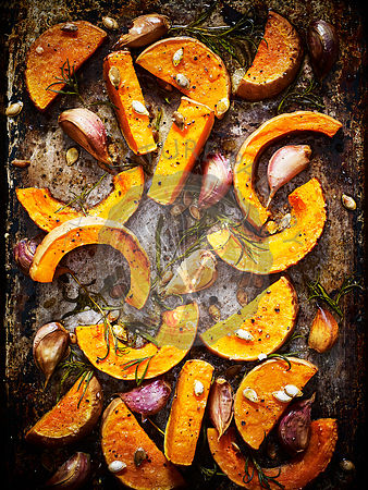 Roasted sliced pumpkins with garlic cloves and herbs