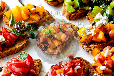 Closeup view of bruschetta with fresh basil and diced heirloom tomatoes.