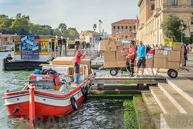 VENICE, ITALY - OCTOBER 26, 2017: Couriers offloading parcels from a barge close to the train station in Venice.