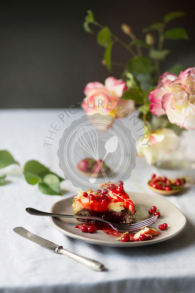 Two slices of cheesecake with redcurrants on a table