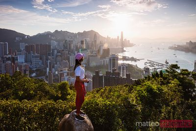 Asian woman looking at Hong Kong skyline at sunset