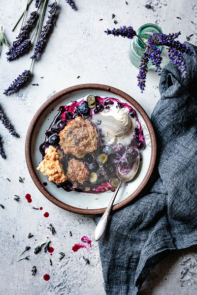 Blueberry cobbler in a bowl with ice cream and lavender.