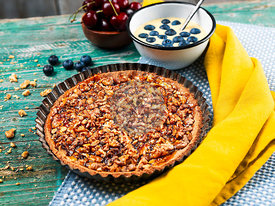 Homemade walnut tart with cherry jam, cherries, blueberries, vanilla curd on a wooden table