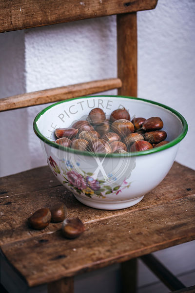 Chestnuts in a bowl on a rustic old wooden table