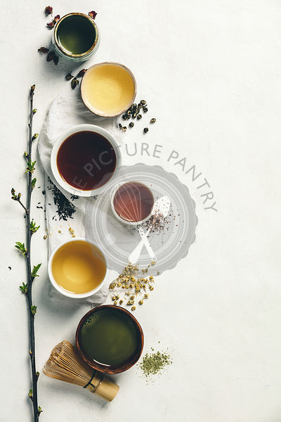 Cups of tea with aromatic dry tea in bowls on a white vintage background