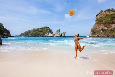 Woman throwing her hat and jumping at the beach, Bali