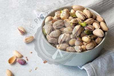 Roasted pistachio nuts in a bowl.