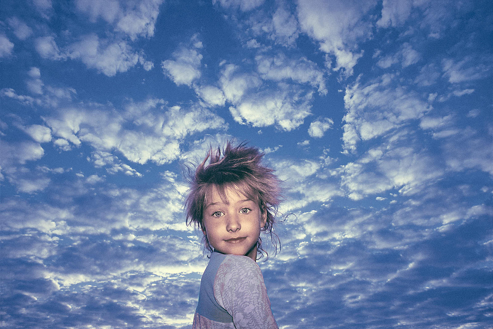 01-portrait-of-morning-child-against-a-deep-blue-sunrise-sky-skattered-with-clouds