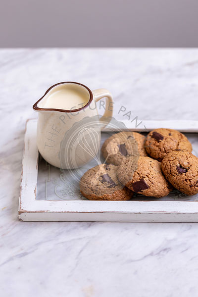 Oats chocolate chip cookies and a jug of milk on a tray