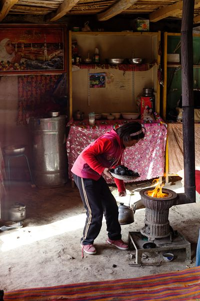 Kyrgyz young girl putting coal in the stove