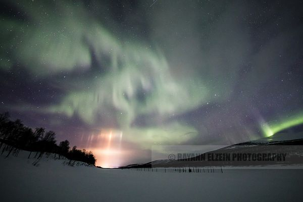 Light pillars of the Sami bridge and northern lights above the Teno River in Utsjoki in Finnish Lapland