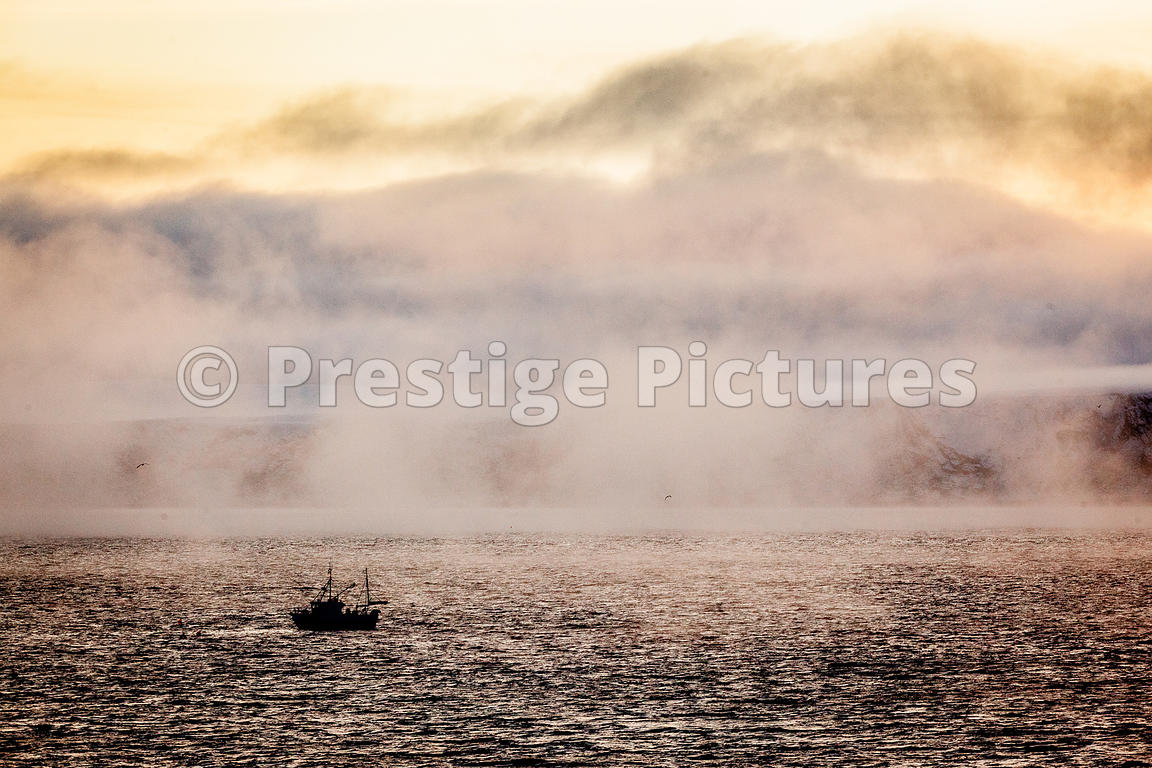Small Fishing Boat in moody misty waters