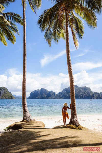 Woman standing between palm trees, El Nido