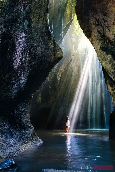 Woman at a waterfall illuminated by a sunbeam, Bali