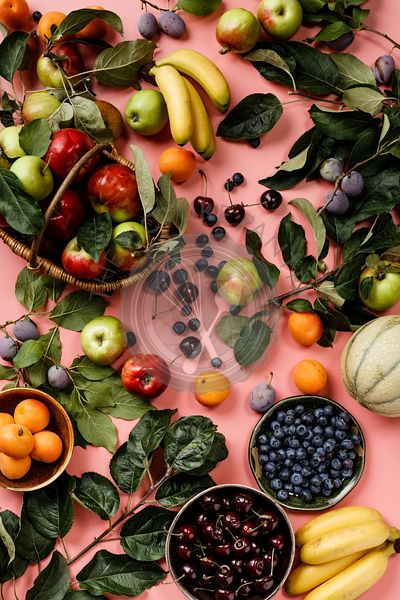 Flat-lay of fresh fruits and berries on pink background