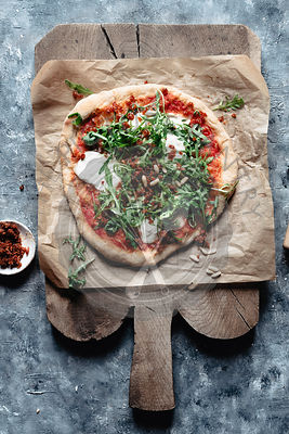 A rustic vegetarian pizza with beans and arugula and mozzarella cheese