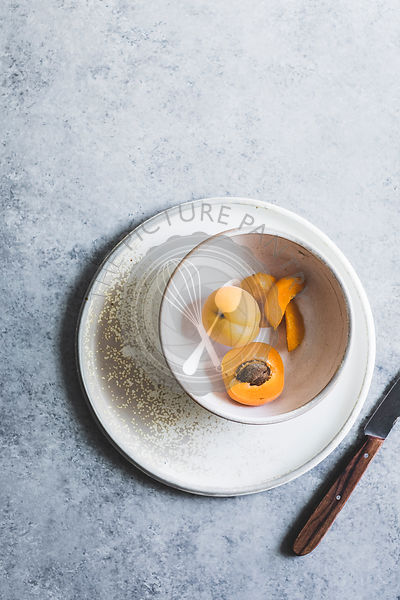A sliced apricot in a bowl