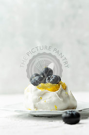 Mini lemon curd pavlovas on a white background