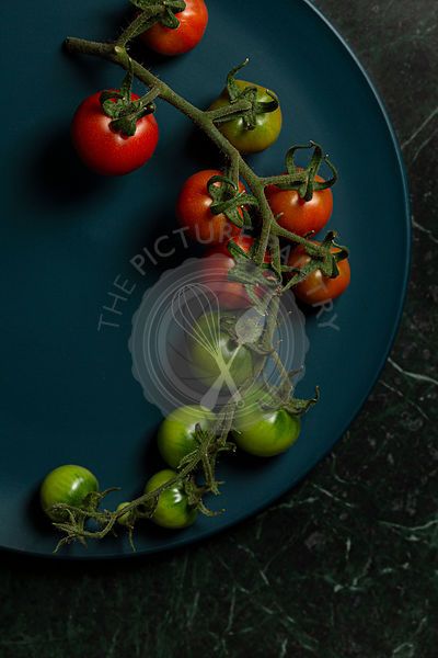 Cherry tomatoes on the vine, some ripe and some unripe, on a teal blue plate, on a green marble background.