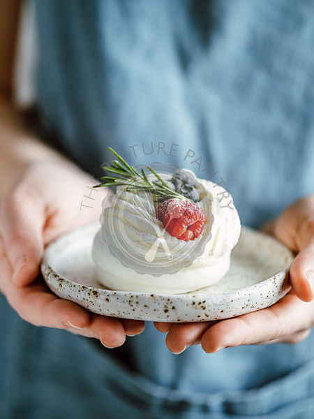 Woman with mini Pavlova cake in plate
