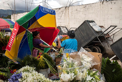 Two indigenous women pack away their flower stall