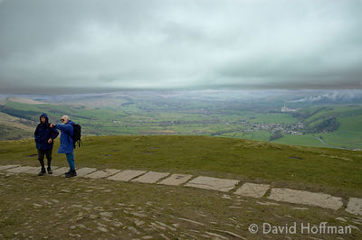 Walkers on Mam Tor in the Peak District National Park, Derbyshire as rain approaches.