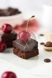 Chocolate pastry with cherry on with table