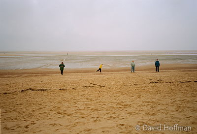 Holidaymakers walking on the deserted beach at Wells Next The Sea in north Norfolk.part of this photo to be stored, reproduce...