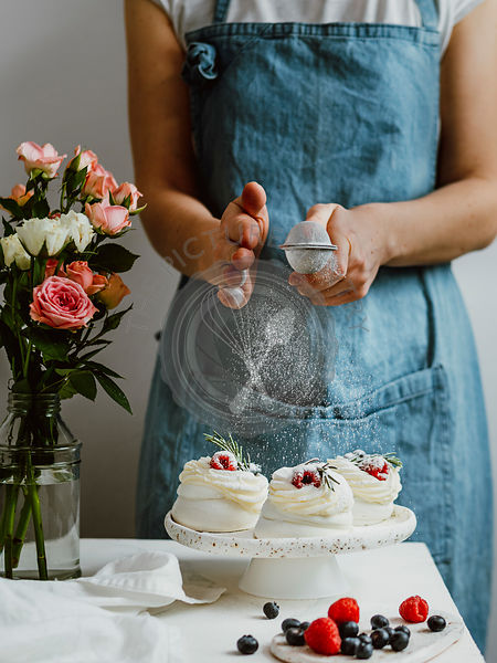 Woman sprinkles icing sugar on mini Pavlova cakes with fresh berries