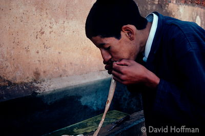 Boy cleans inestines by blowing water through them at a slaughterhouse in Essouaria, Morocco. 1991.