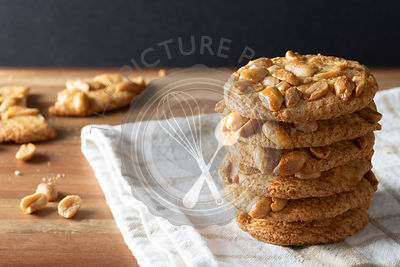 A stack of crisp peanut biscuits with a broken biscuit in the bakground.